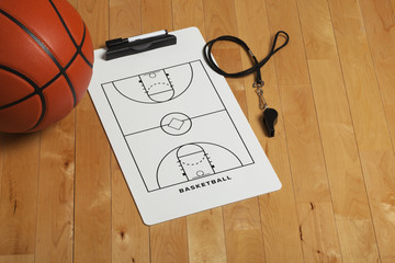 Basketball with coach's clipboard and whistle on wooden floor