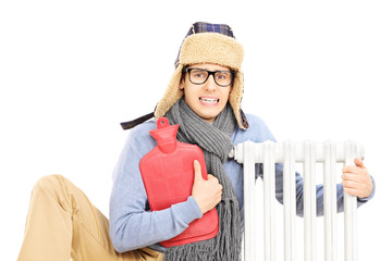 Chilled young man with hot water bottle hugging a radiator