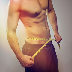 Fit young man measuring waist