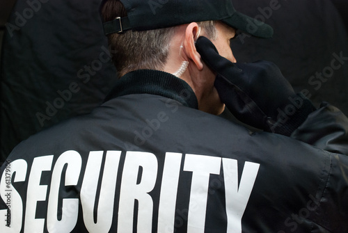Leinwandbild Motiv Security Guard Listens To Earpiece, Back of Jacket Showing