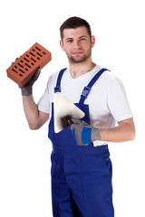 Builder standing with brick and spatula