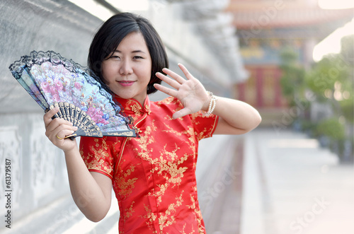 asian woman wearing a cheongsam with folding fan