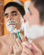 Young hispanic man shaving