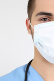 Young male doctor in medical mask, close-up, isolated on white