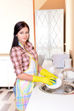 Beautiful young woman washing dishes in kitchen