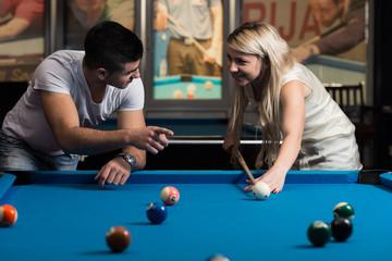 Man Teaching Woman How To Play Pool