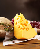 Piece of cheese with grape and rosemary