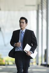 Asian businessman running through city