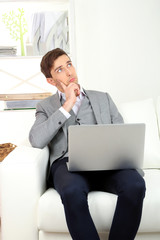 Young businessman using laptop on sofa at home