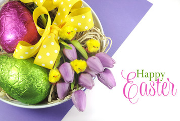 Happy Easter basket of chocolate eggs and tulips