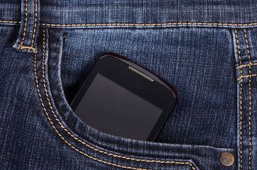 Part of cellphone in the front pocket of blue jeans
