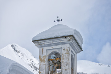 mountain bell tower covered by snow