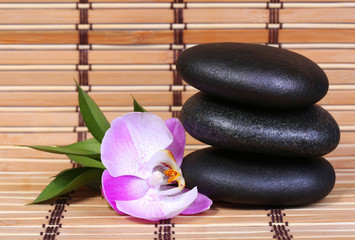 Spa Stones and Pink Orchid Flower with Leaves on bamboo mat