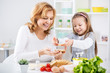 Grandmother and granddaughter making a Sandwich.
