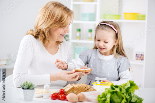 Grandmother and granddaughter making Sandwich.