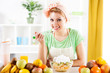 Beautiful young woman eat fruit salad in the kitchen.