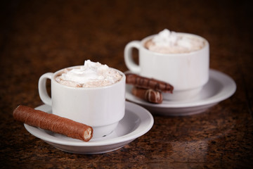 Two cups of coffee or hot cocoa with chocolates and  cookies on