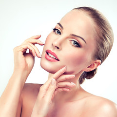 Beautiful girl with clean and fresh skin, touching her face.
