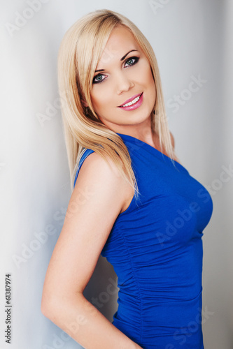 Portrait of a blonde in a blue dress on a light background