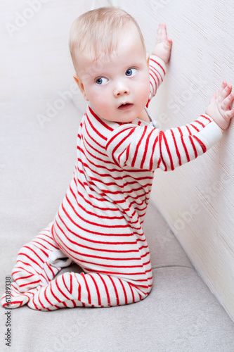 Cute baby boy learning to crawl and stand up