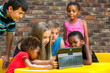 Diverse group of kids looking at tablet. - 61389578