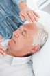 Man receiving Reiki treatment by therapist