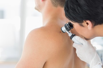 Doctor examining mole on back of man