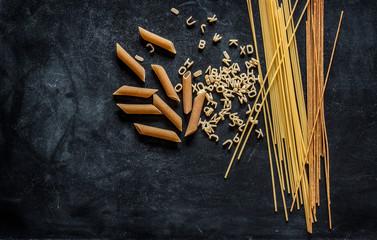 Different kinds of pasta on black chalkboard
