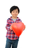 Smiling Chinese boy holding a red heart, isolated on white