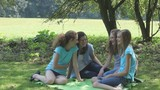 four young teenagers sitting in the park for a walk and have fun