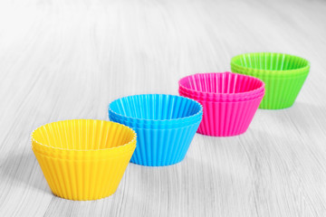 Colorful silicone baking cups on wooden background.