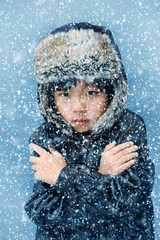 Cute boy with hat feeling cold in the winter snow