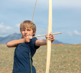 Boy shoots a bow at a target