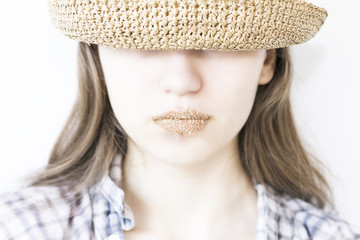 girl, straw hat and sand on the lips