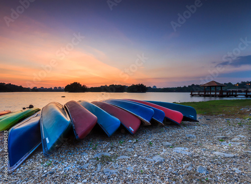 A bunch of kayaks stranded with a sunset view.