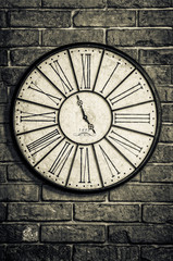 Old vintage clock in monochrome on textured brick wall