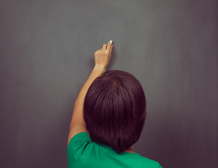 Woman writes on the blackboard