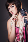 Beautiful singer singing with a retro microphone in studio