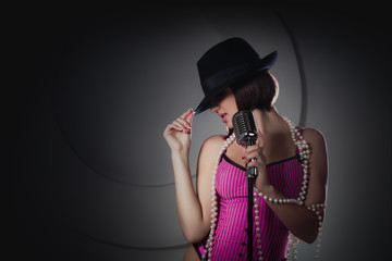 Beautiful singer in black hat singing with a retro microphone
