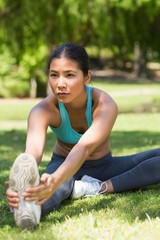 Healthy and beautiful woman stretching hands to leg in park