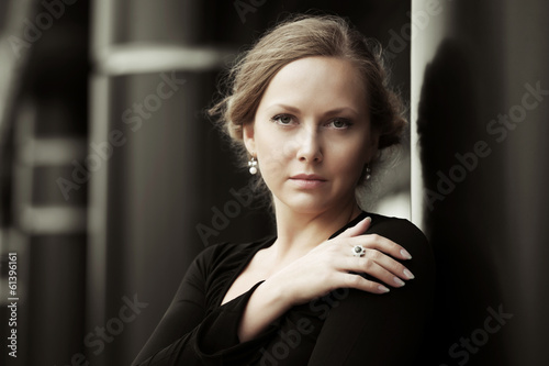 Beautiful woman in black dress at the wall