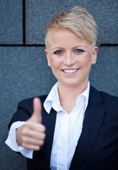 Confident businesswoman showing thumbs up