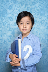 Chinese school boy holding a study book