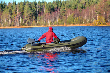 Green, powerboat, inflatable rubber boat with motor on wood lake
