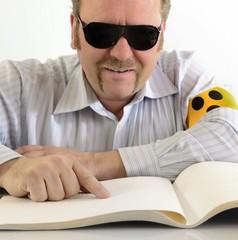 Mann liest Braille Blindenschrift