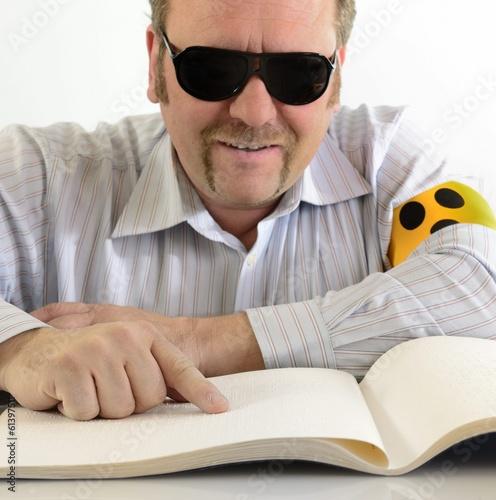 Leinwandbild Motiv Mann liest Braille Blindenschrift
