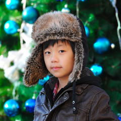 Cute Asian boy with winter hat in front of Christmas tree