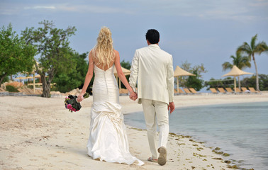 Bride and groom walking together on beach