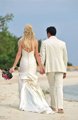 Wedding couple walking on beach