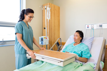 Nurse Placing Overbed Table For Male Patient